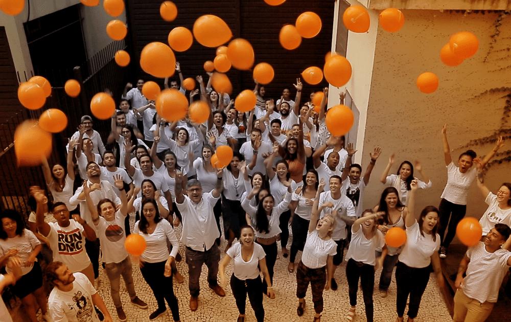 Foto com toda a equipe de branco lançando balões laranja para o céu